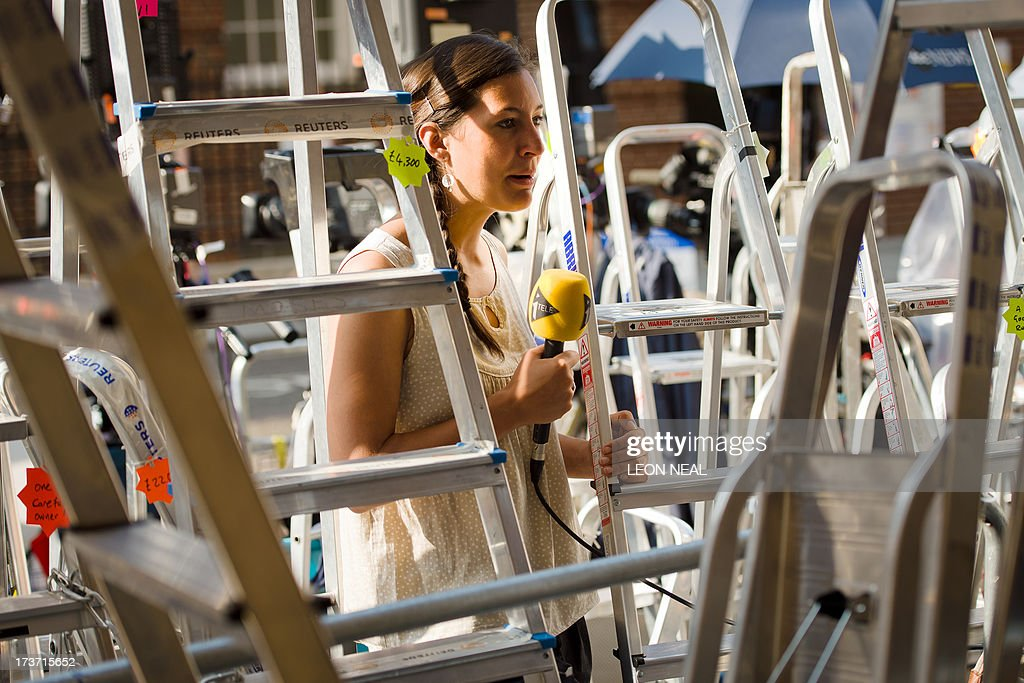A television presenter records a piece to camera as she stands amongst photographers ladders outside the Lindo Wing of Saint Mary's Hospital in London, on July 17, 2013, where Prince William and his wife Catherine's baby is expected to be born. Britain's Prince Charles joked Monday that his son Prince William's baby was 'hopefully' on the way, but wife Camilla went further, saying it could arrive 'by the end of the week'.