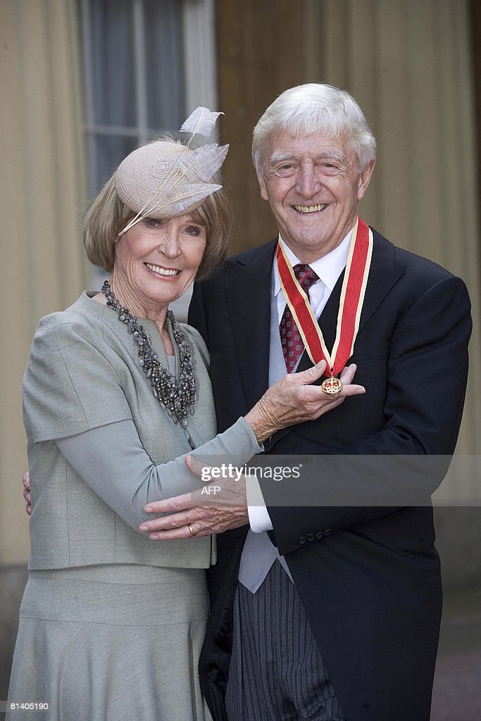 Television presenter Sir Michael Parkinson (R) poses for photographs with his wife Mary after receiving his Honour of Knighthood from Britain's Queen <a gi-track='captionPersonalityLinkClicked' href=/galleries/search?phrase=Elizabeth+II&family=editorial&specificpeople=67226 ng-click='$event.stopPropagation()'>Elizabeth II</a> at Buckingham Palace, in London, on June 4, 2008. AFP PHOTO/Jenny Goodall/POOL
