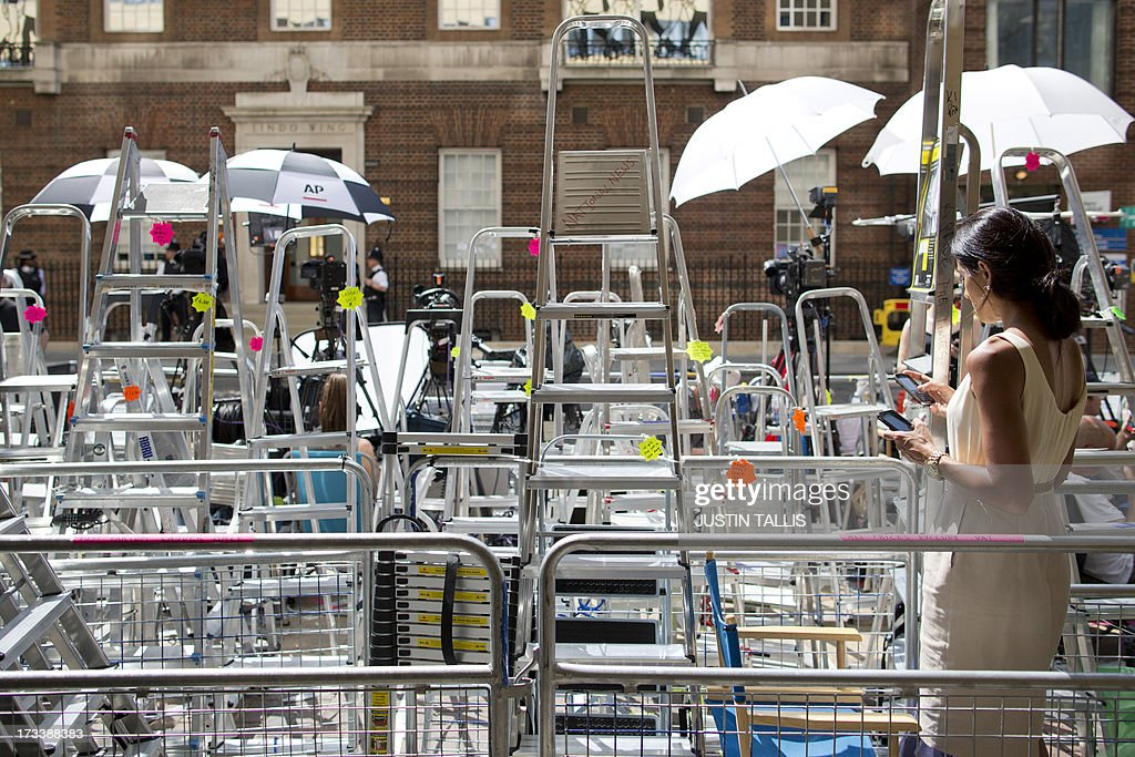 A television presenter works on her mobile phone among media stepladders outside the Lindo Wing of Saint Mary's Hospital in London, on July 13, 2013, where Prince William and his wife Catherine's baby will be born. Britain's royal family and the world's media are on tenterhooks awaiting the birth of Prince William and wife Catherine's first child, a baby who will one day be king or queen of Britain and a diverse group of commonwealth countries.
