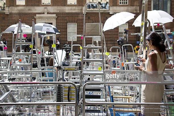 A television presenter works on her mobile phone among media stepladders outside the Lindo Wing of Saint Mary's Hospital in London on July 13 where...