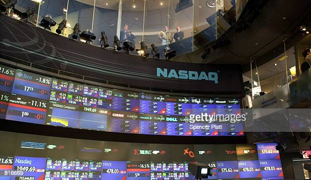 A television reporter explains the drop in the Nasdaq March 12 2001 at the Nasdaq MarketSite in New York City as pedestrians look down into the...