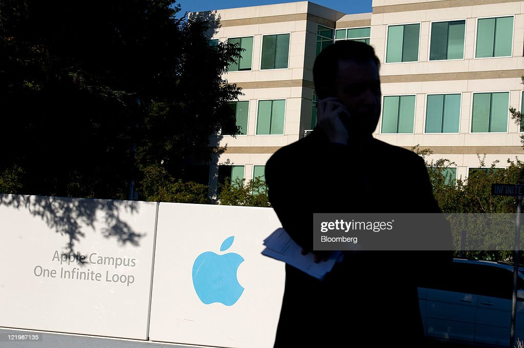 A television reporter talks on a mobile phone in front of Apple Inc. signage outside the company's headquarters in Cupertino, California, U.S., on Wednesday, Aug. 24, 2011. Apple Inc. chief executive officer Steve Jobs, who transformed the company he started at age 21 from a personal-computer also-ran into the world's largest technology company, resigned today. Photographer: David Paul Morris/Bloomberg via Getty Images