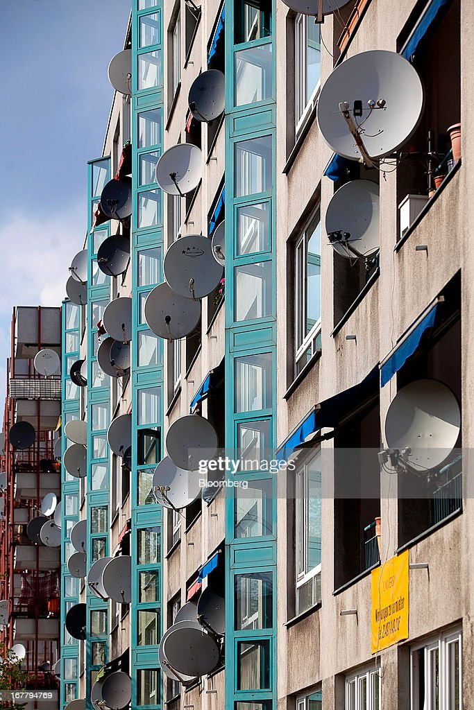 Television satellite dishes cover the exterior of a block of residential housing located in the Wedding suburb of Berlin, Germany, on Monday, April 29, 2013. Rents and home prices in Germany's largest cities are rising at the fastest rate in twenty years, according to data compiled by Bulwien Gesa AG. Photographer: Krisztian Bocsi/Bloomberg via Getty Images
