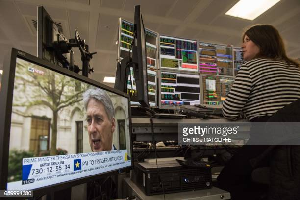 A television screen displays a 'Brexit Dealine' countdown timer as British Chancellor of the Exchequer Philip Hammond is interviewed whislt a trader...