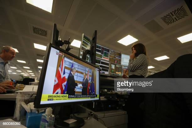 A television screen displays a picture of Britain's ambassador Tim Barrow delivering a letter to European Union President Donald Tusk as a broker...