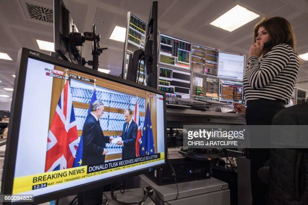 A television screen displays an image of Britain's ambassador to the EU Tim Barrow as he delivers British Prime Minister Theresa May's letter giving...