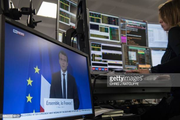 A television screen displays an image of France's Presidentelect Emmanuel Macron as traders works on the trading floor of ETX Capital in London on...