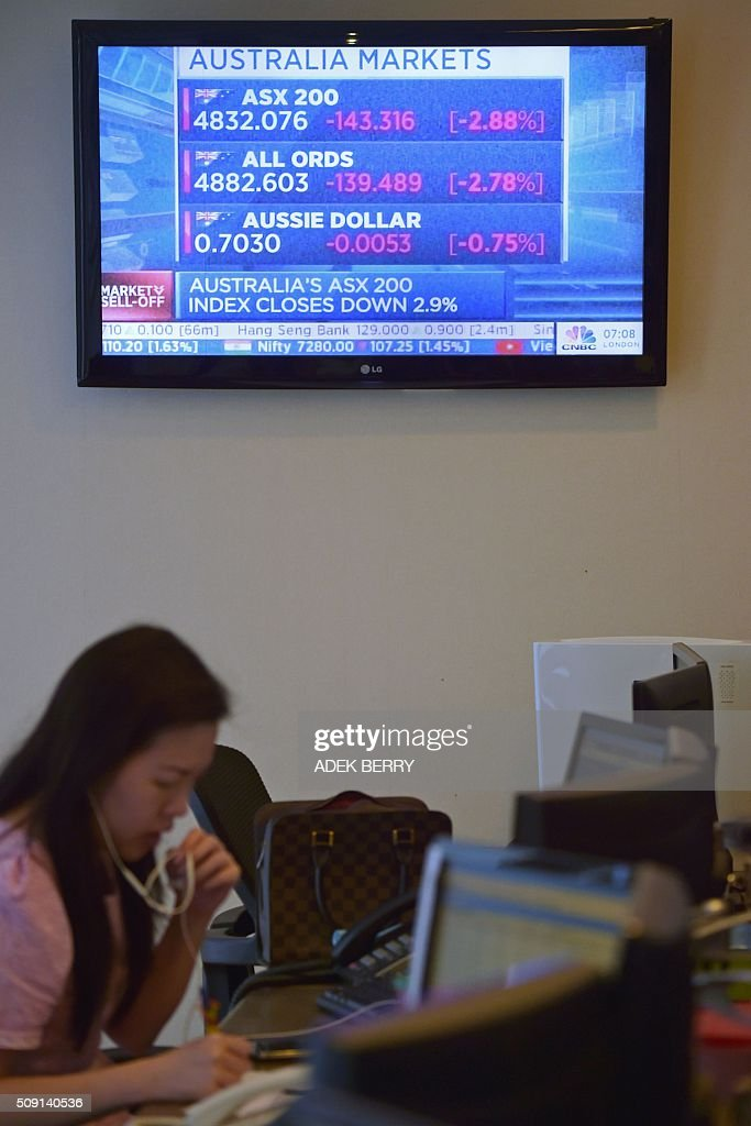 A television screen shows a market report as an Indonesian trader works at a securities office in Jakarta on February 9, 2016. The Indonesian stock market reopened February 9 while most of the Asian region remained closed for the Lunar New Year holiday, as trading remained thin but dealers took their lead from New York and Europe where banking shares were battered. AFP PHOTO / ADEK BERRY / AFP / ADEK BERRY