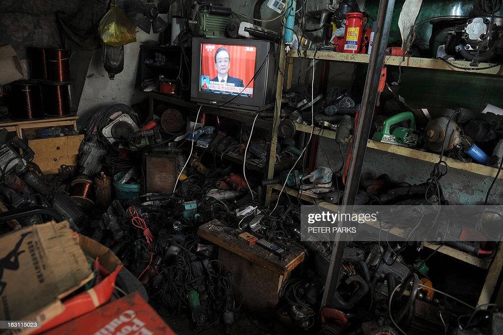 A television set shows Chinese Premier Wen Jiabao (L) speaking at the opening session of the National People's Congress (NPC), in a parts repair shop in Shanghai on March 5, 2013. Premier Wen targeted 2013 growth of 7.5 percent and vowed an unwavering fight against corruption as the world's second-largest economy opened its annual parliamentary session. AFP PHOTO/Peter PARKS