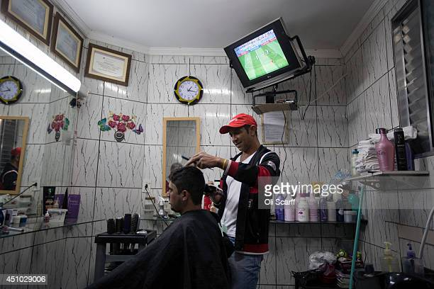 A television shows a World Cup match in a barber shop in the poor neighbourhood of Itaquera adjacent to the 'Arena de Sao Paulo' stadium on June 21...