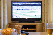 Television, TV watching (baseball match) with snacks and alcohol lying on table - stock photo