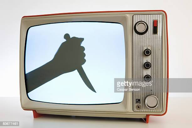 A television with a black and white image of a human hand holding a knife, silhouette