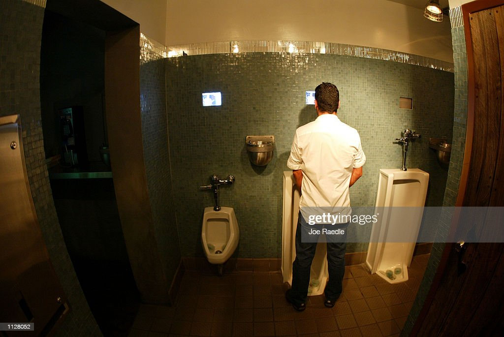 Televisons are mounted into the wall above the urinals at the South Beach's Pelican Hotel July 16 2002 in Miami Beach Florida More and more bathrooms...