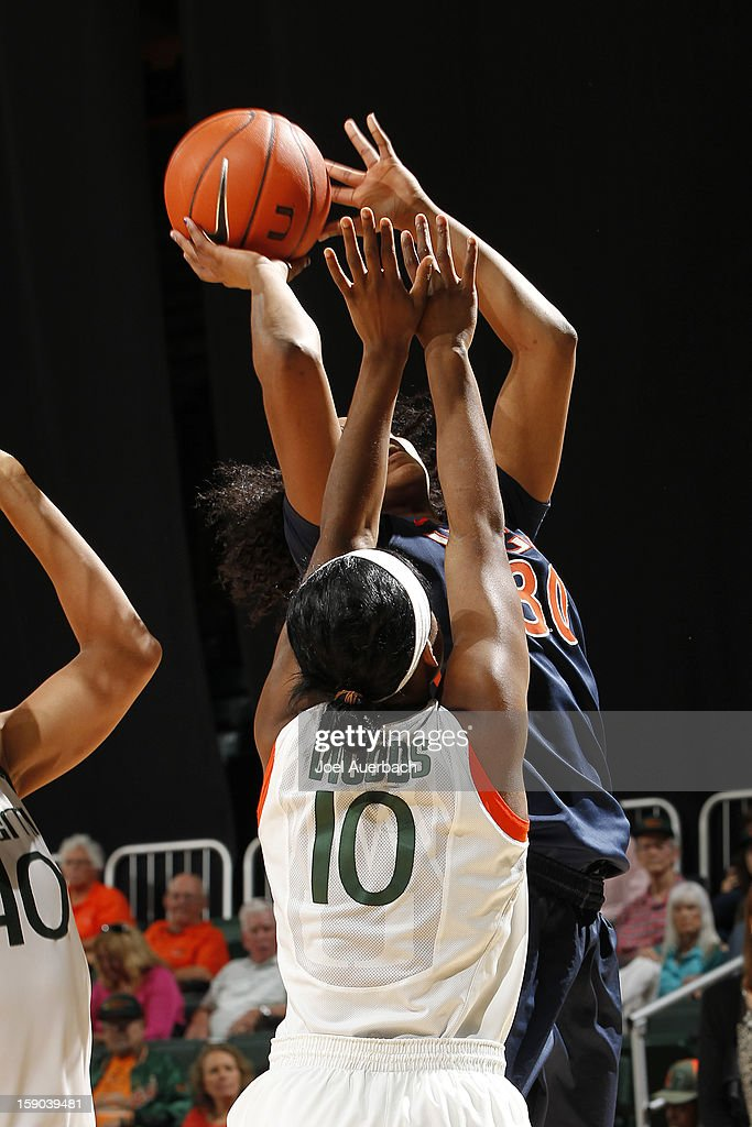Telia McCall #30 of the Virginia Cavaliers goes to the basket while being defended by Michelle Woods #10 of the Miami Hurricanes on January 6, 2013 at the BankUnited Center in Coral Gables, Florida. The Hurricanes defeated the Cavaliers 58-52.