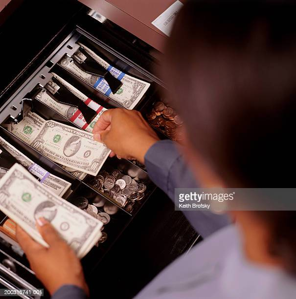 Teller counting money at cash register, elevated view