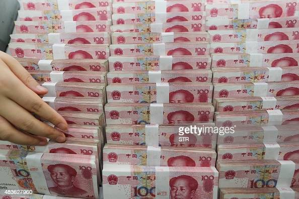 A teller counts yuan banknotes in a bank in Lianyungang east China's Jiangsu province on August 11 2015 China's central bank on August 11 devalued...