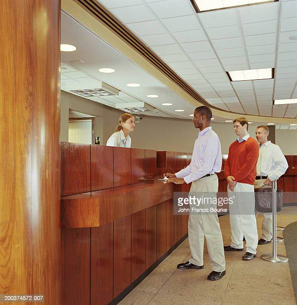 Teller helping customer in bank