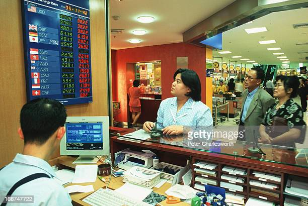 A teller serves customers at a small Bank of Asia 'kiosk' inside a large Central department store in downtown Bangkok In the background the checkout...