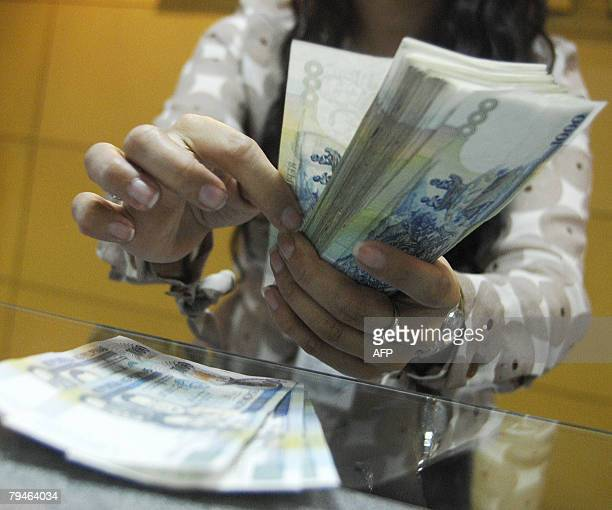 A teller shows thousand peso bills inside a bank at the Makati financial district in Manila 1 February 2008 Philippine monetary authorities trimmed...