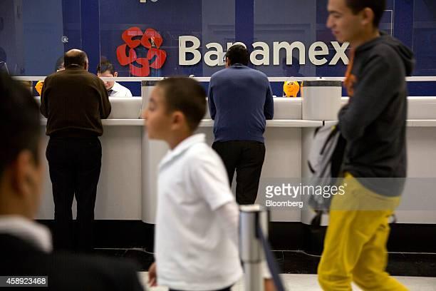 Tellers help customers at a Banco Nacional de Mexico SA branch in Mexico City Mexico on Thursday Nov 13 2014 Banamex a subsidiary of Citigroup Inc...