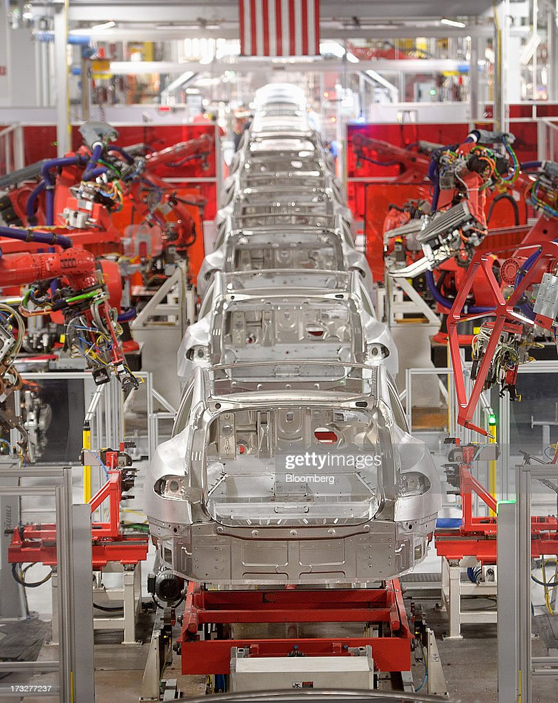 Telsa Motor Inc. Model S sedans make their way along a robotic assembly line at the company's assembly plant in Fremont, California, U.S., on Wednesday, July 10, 2013. Tesla is building Model S electric sedans faster than its initial 400-a-week goal as demand and the companys production skills increase, Chief Executive Officer Elon Musk said. Photographer: Noah Berger/Bloomberg via Getty Images