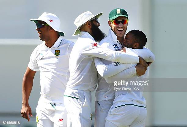 Temba Bavuma of South Africa celebrates with Faf du Plessis and Hashim Amla of South Africa after taking the wicket of Josh Hazlewood of Australia...