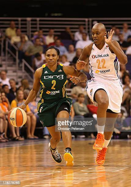 Temeka Johnson of the Seattle Storm moves the ball past Charde Houston of the Phoenix Mercury during the WNBA game at US Airways Center on August 23...