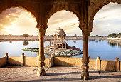 Arches and temple in Gadi Sagar lake at sunset sky in Jaisalmer, Rajasthan, India