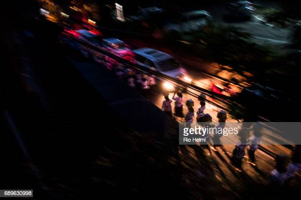 STREET UBUD BALI INDONESIA A temple procession with women carrying offerings on their heads goes down the street in Ubud late at night with villagers...
