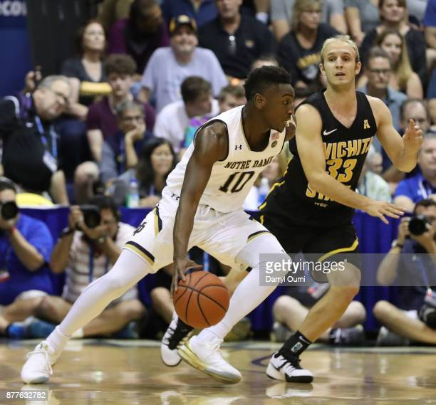 Temple 'TJ' Gibbs Jr #10 of the Notre Dame Fighting Irish dribbles around Conner Frankamp of the Wichita State Shockers during the first half at the...