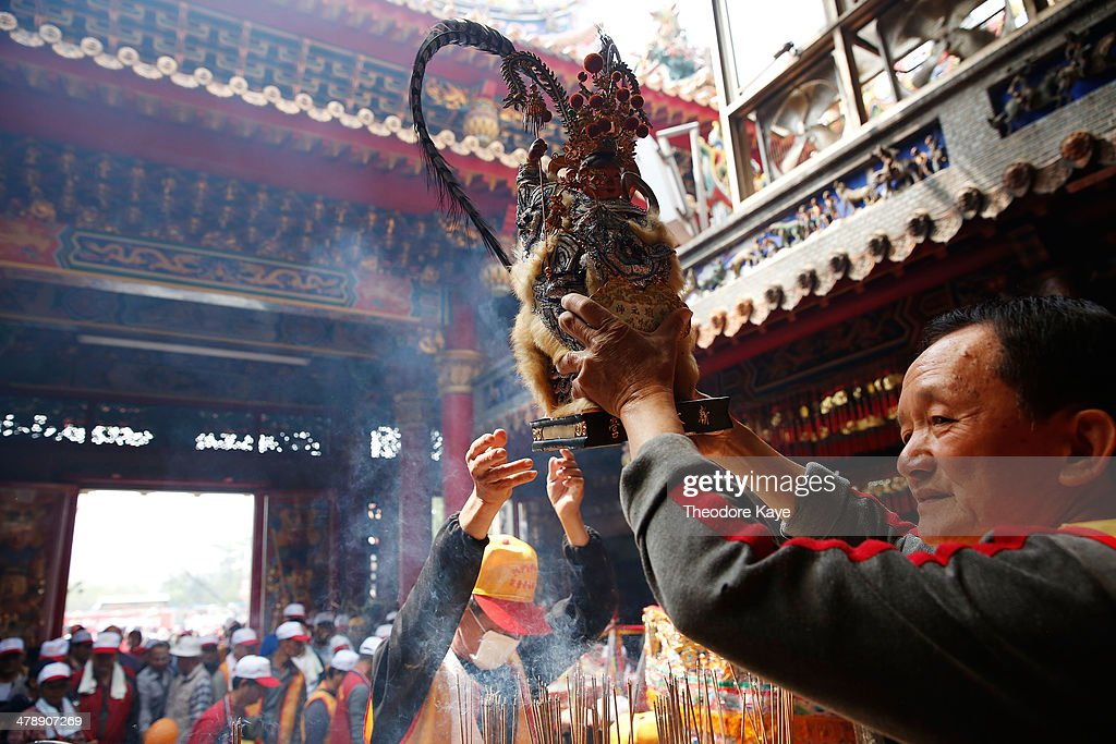 A temple volunteer carries a god figure over an incense urn at the Zizhu temple on March 15, 2014 in Neimen, Kaoshiung, Taiwan. Songjiang Battle Array or Song Jiang Zhen is a folk martial art particular to Taiwan. The martial art dates to the Ming Dynasty and draws inspiration from the Chinese epic novel, 'Outlaws of the Marsh.' A lot of the weapons used in the martial art were originally modifications of agricultural implements and farming tools, as it evolved as a self-defense military tactic for Taiwanese farmers against invaders. Every year, an intercollegiate Songjiang Battle Array competition is held in Neimen, coinciding with the festival marking the birthday of Guanyin Buddha.