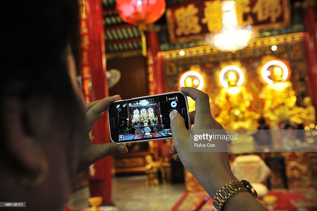 A temple-goer uses a smartphone to capture the interior of a shrine in Chinatown during festivities welcoming in the Chinese New Year on January 31, 2014 in Bangkok, Thailand. Despite a government declared state of emergency and ongoing anti-government protests in the run-up to the general election on February 2nd, festivities were held in Bangkok's Chinatown ushering in the Chinese New Year.