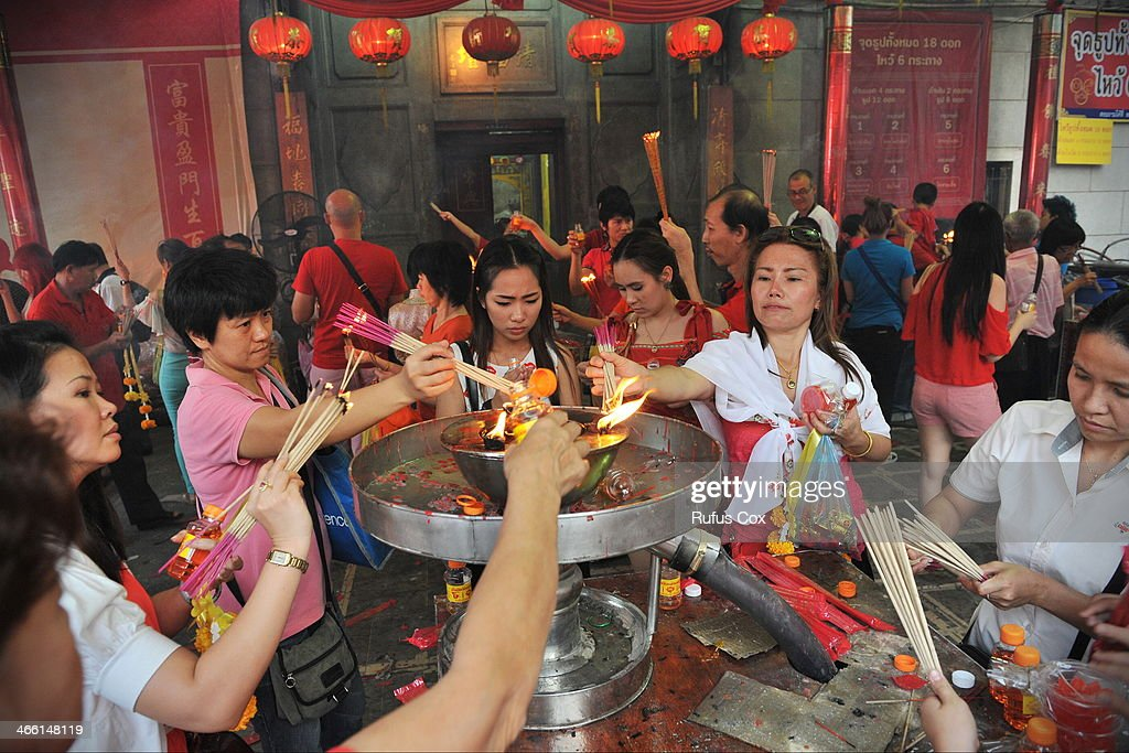 Temple-goers incense and candles at a shrine in Chinatown during festivities welcoming in the Chinese New Year on January 31, 2014 in Bangkok, Thailand. Despite a government declared state of emergency and ongoing anti-government protests in the run-up to the general election on February 2nd, festivities were held in Bangkok's Chinatown ushering in the Chinese New Year.
