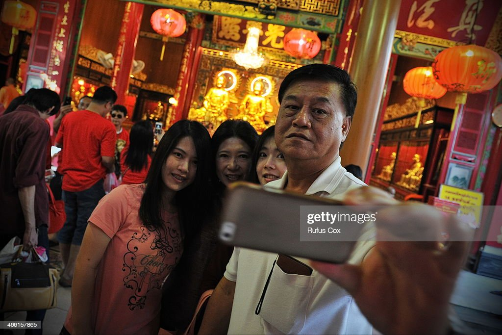 Temple-goers pose for a family portrait at a shrine in Chinatown during festivities welcoming in the Chinese New Year on January 31, 2014 in Bangkok, Thailand. Despite a government declared state of emergency and ongoing anti-government protests in the run-up to the general election on February 2nd, festivities were held in Bangkok's Chinatown ushering in the Chinese New Year.