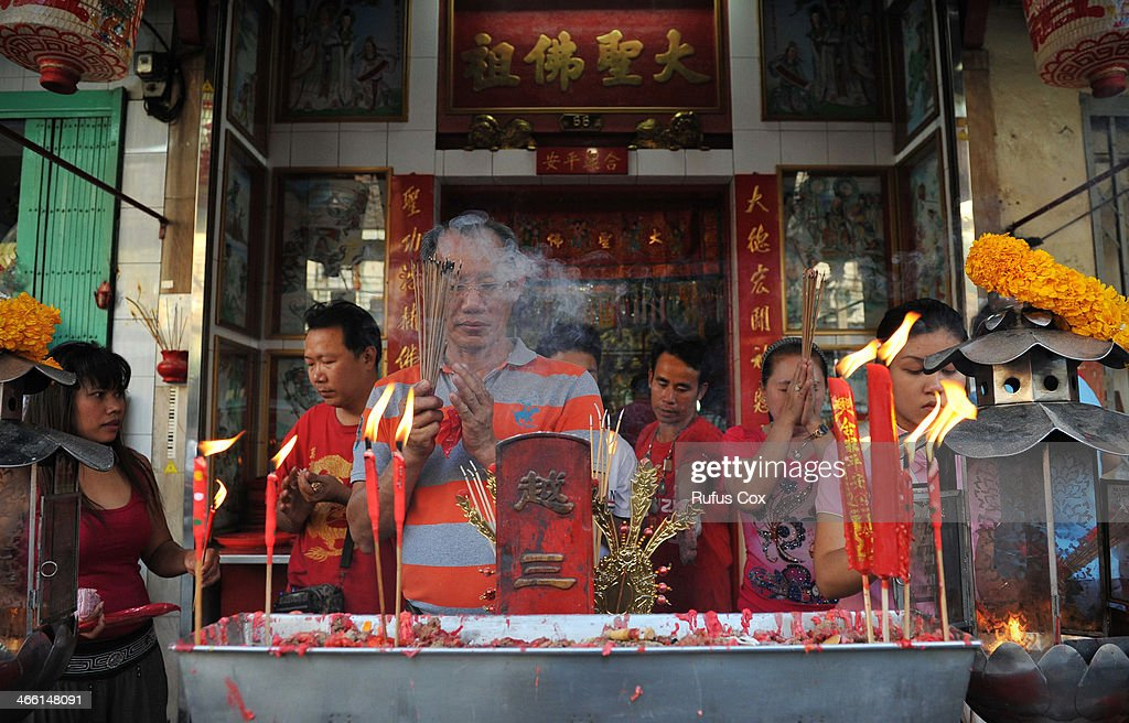 Temple-goers pray at a shrine in Chinatown during festivities welcoming in the Chinese New Year on January 31, 2014 in Bangkok, Thailand. Despite a government declared state of emergency and ongoing anti-government protests in the run-up to the general election on February 2nd, festivities were held in Bangkok's Chinatown ushering in the Chinese New Year.