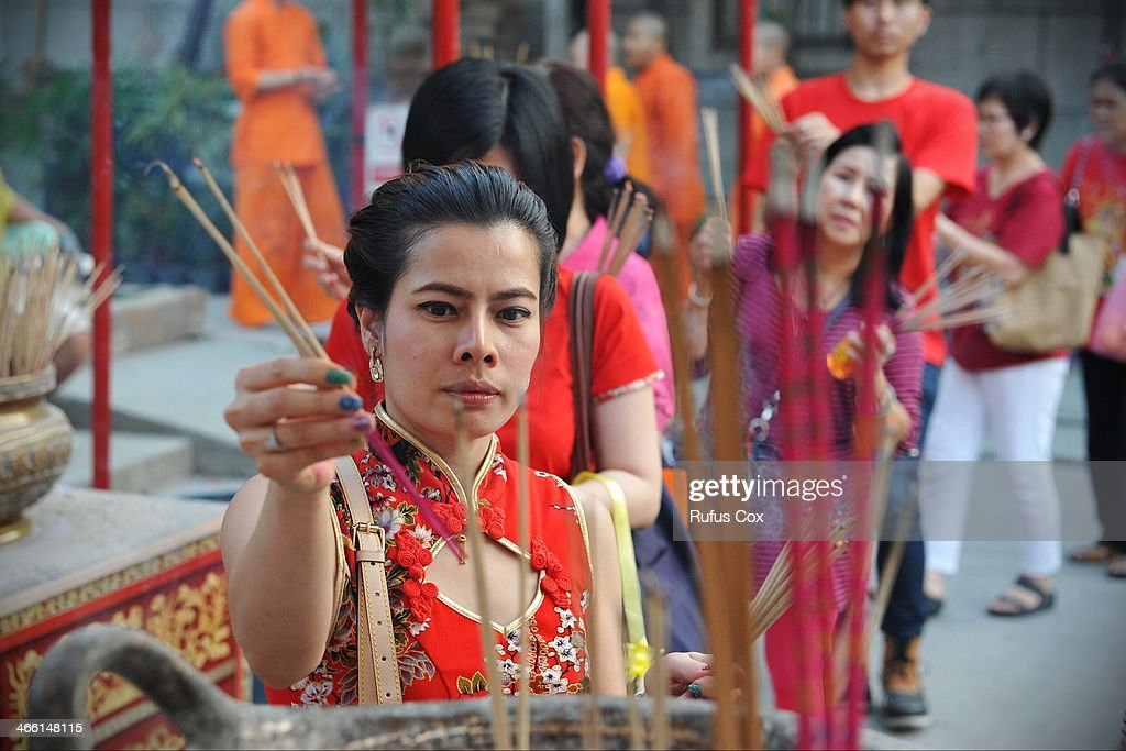 Temple-goers take part in a merit-making ceremony at a shrine in Chinatown during festivities welcoming in the Chinese New Year on January 31, 2014 in Bangkok, Thailand. Despite a government declared state of emergency and ongoing anti-government protests in the run-up to the general election on February 2nd, festivities were held in Bangkok's Chinatown ushering in the Chinese New Year.