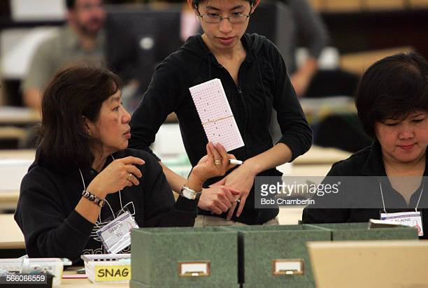 Temporary Election Worker Senen Yu shows SNAG ballots to management analyst Quyen Doan as her colleague Laeaine Minas works on another stack of...