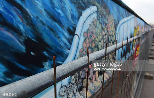 A temporary fence protects wall paintings on the East Side Gallery a muchvisited stretch of the Berlin wall while graffiticleaning work is underway...