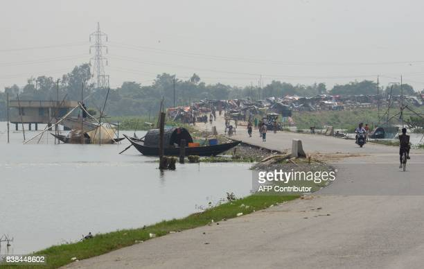 Temporary tents are set up on the roadside by flood affected villagers in Malda in the Indian state of West Bengal on August 24 2017 The death toll...