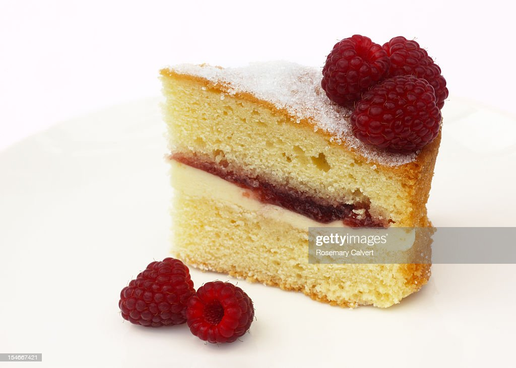 Tempting slice of Victoria sponge with raspberries : Stock Photo