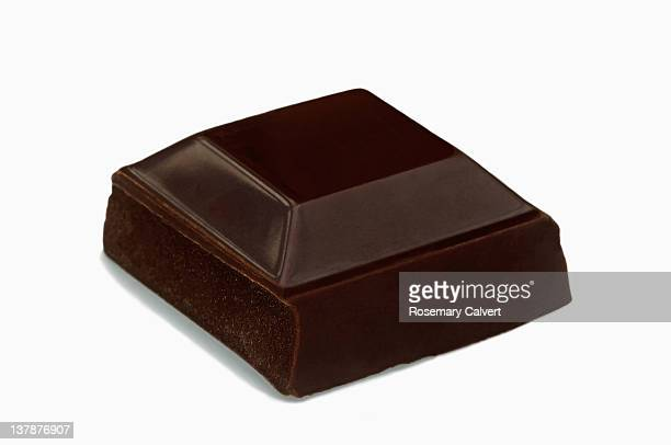 Tempting square of dark chocolate ready to eat.