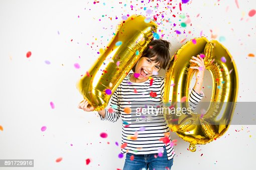 Ten birthday party girl with golden balloons and confetti : Stock Photo