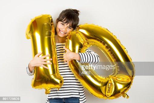 Ten birthday party girl with golden balloons : Stock Photo