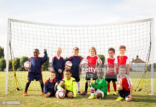 Ten children standing in football goal