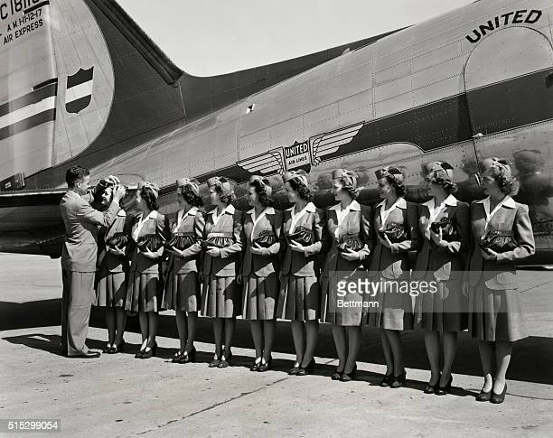 Ten flight attendants pose in uniform beside a United Air Lines jet They are shown standing in a neat row holding matching purses and watching as a...