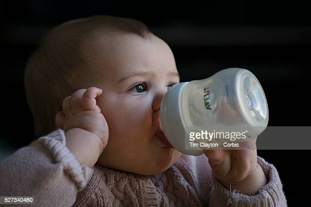 A ten month old baby girl peering out of the window while feeding herself with a bottle of milk Photo Tim Clayton
