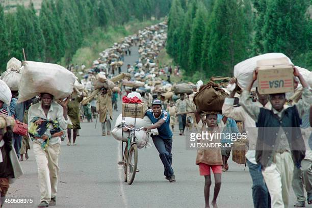 Ten of thousands of Rwandan Hutu refugees carry their belongings as they flee towards the Tanzanian border from the refugee camps at Magara near the...