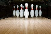 Ten pin bowling alley background. Closeup of tenpin row on a lane, night light.