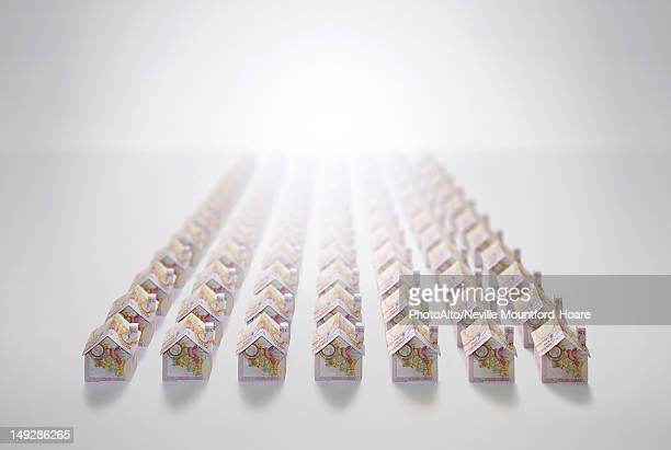 Ten pound notes folded into the shapes of houses