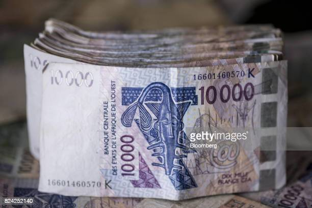 Ten thousand West African CFA franc currency banknotes sit in this arranged photograph in Dakar Senegal on Saturday July 29 2017 Senegalese voters...